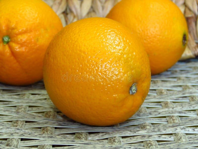 Feche acima de três laranjas amarelas alaranjadas suculentas no fundo tecido feito a mão dos trabalhos do bambu do bastão de ratt fotos de stock