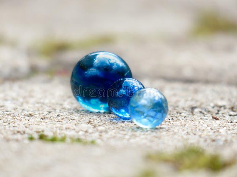 Feche acima de três mármores de vidro azuis no alinhados junto com o espaço borrado do fundo para colocar o texto imagens de stock royalty free