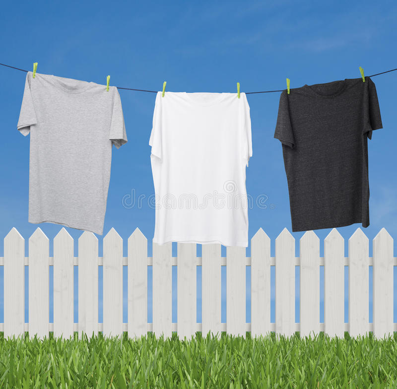 Feche acima de três t-shirt no cinza escuro da corda (cinza, branco e) foto de stock