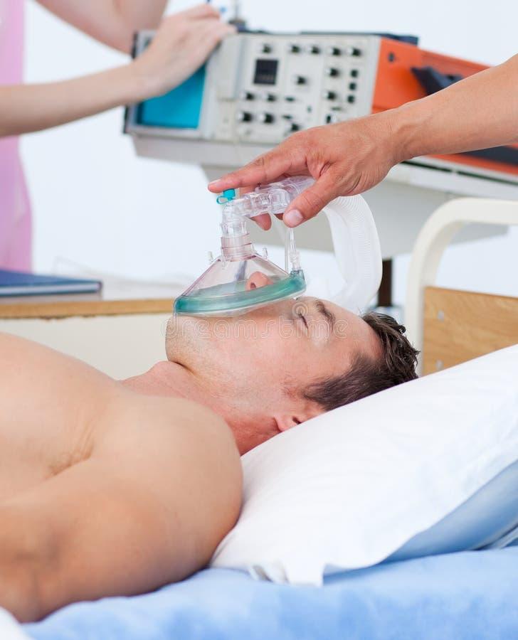 Feche acima de um anesthetist que põr a máscara de oxigénio sobre imagem de stock royalty free