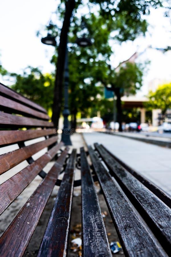 Feche acima de um banco com as árvores verdes no fundo fotografia de stock