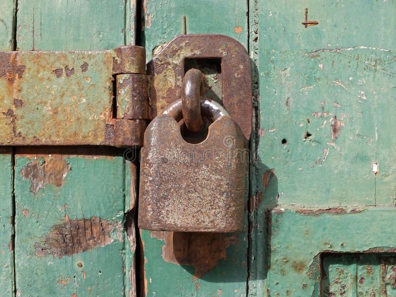 Feche acima de um cadeado oxidado velho do metal que prende uma barra de ferro em uma porta de madeira verde imagem de stock royalty free