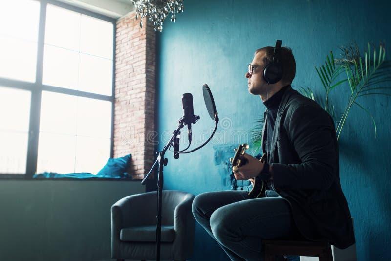 Feche acima de um cantor do homem o assento em um tamborete em fones de ouvido com uma guitarra que grava uma trilha em um est?di imagens de stock royalty free