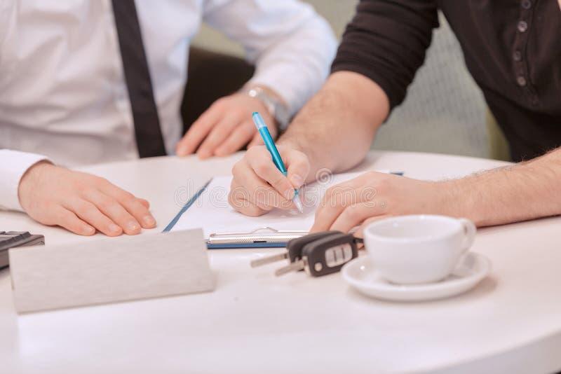 Feche acima de um cliente masculino que assina o contrato imagens de stock royalty free