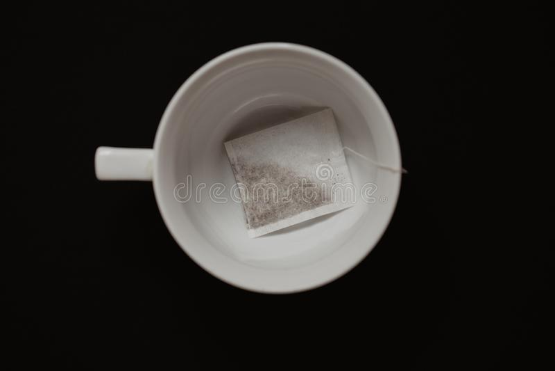 Feche acima de um copo de chá com o saquinho de chá na tabela preta fotos de stock royalty free