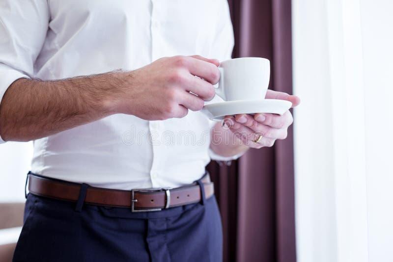 Feche acima de um copo com café nas mãos masculinas imagens de stock