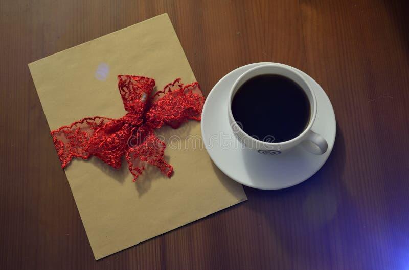Feche acima de um copo de café e de um cartão vazio em uma tabela fotos de stock