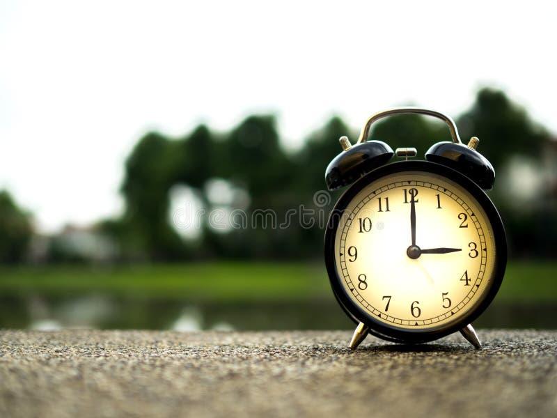 Feche acima de um despertador com fundo da natureza, conceito do tempo imagens de stock