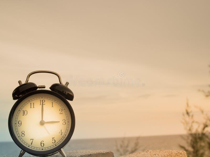 Feche acima de um despertador com fundo da natureza, conceito do tempo imagem de stock royalty free