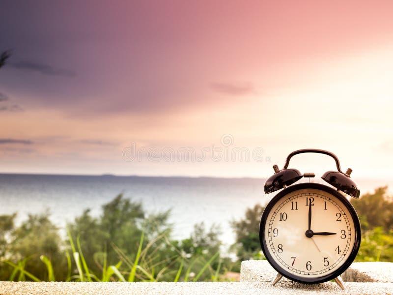 Feche acima de um despertador com fundo da natureza, conceito do tempo imagem de stock