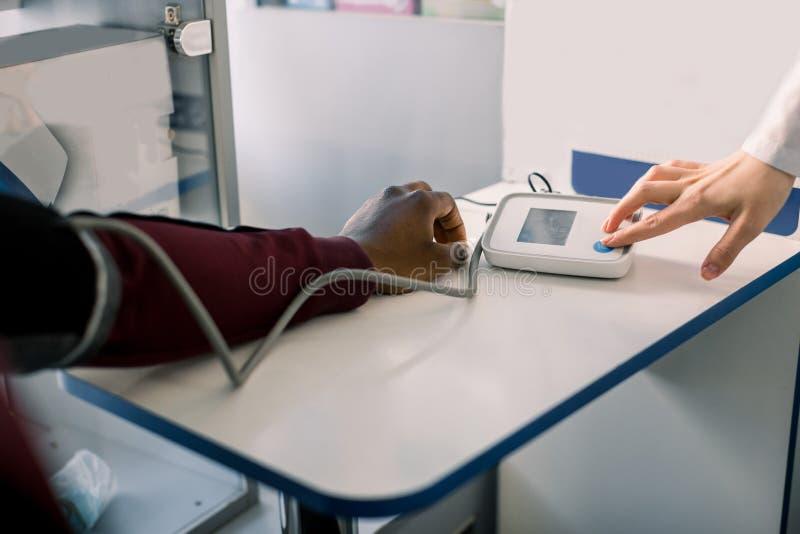 Feche acima de um doutor Checking Blood Pressure de um paciente Pressão sanguínea de medição do cardiologista do doutor do africa fotos de stock royalty free