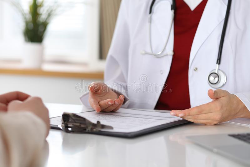 Feche acima de um doutor e das mãos do paciente ao discutir informes médicos após o exame da saúde fotos de stock royalty free