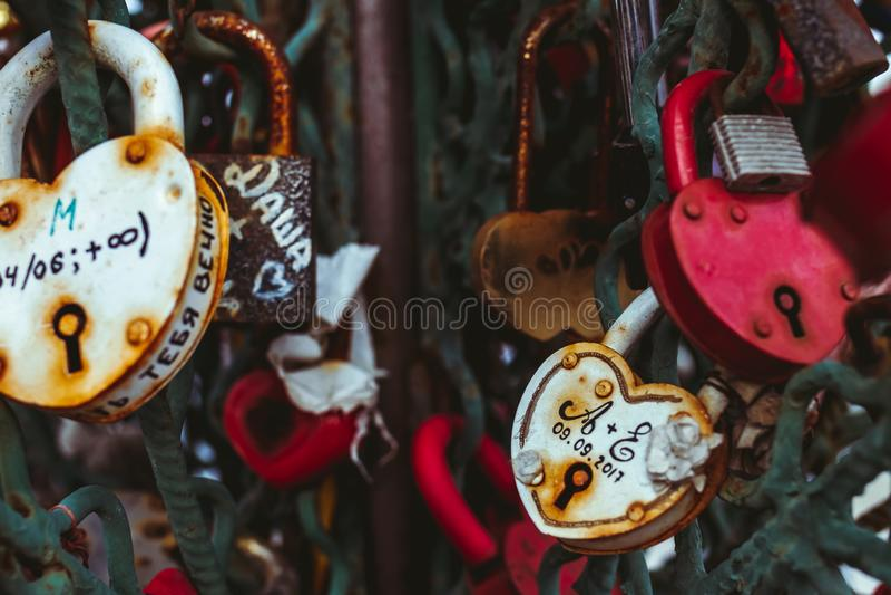 Feche acima de um fechamento do amor em uns trilhos em uma ponte dos fechamentos com outros fechamentos borrados para criar um fu foto de stock
