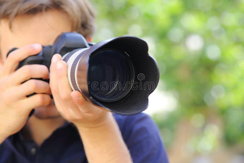 Feche acima de um fotógrafo que usa uma câmera do dslr foto de stock royalty free