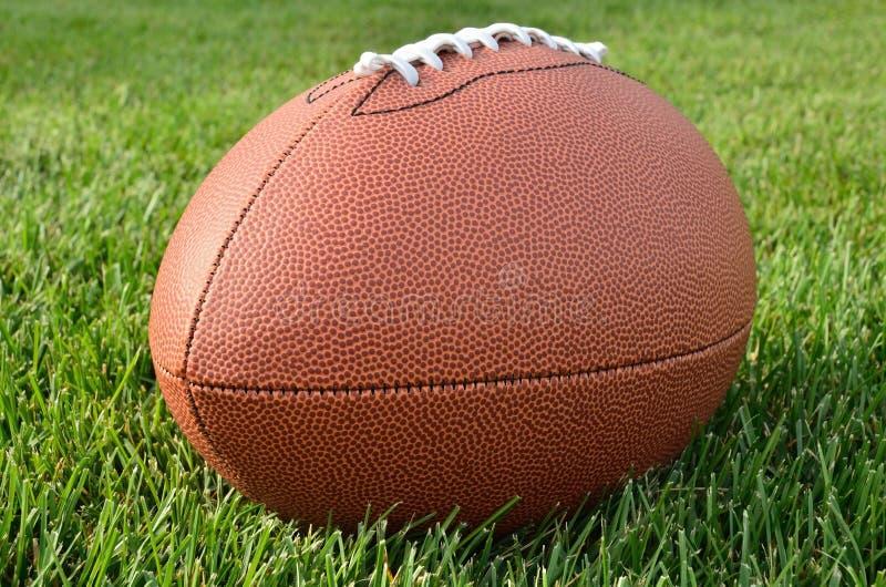Feche acima de um futebol americano no campo de grama foto de stock