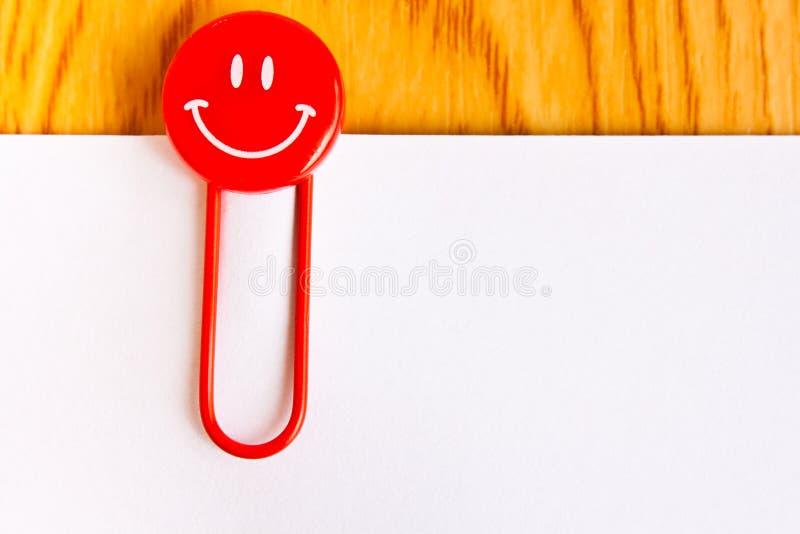 Feche acima de um clipe de papel vermelho e de um Livro Branco imagem de stock royalty free