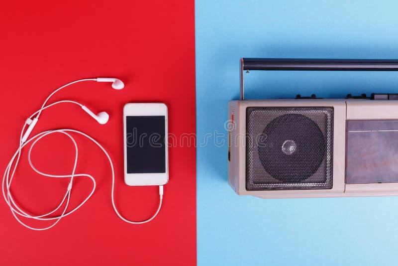 Feche acima de um gravador e de um telefone encontrados fundo coloridos com fones de ouvido imagem de stock