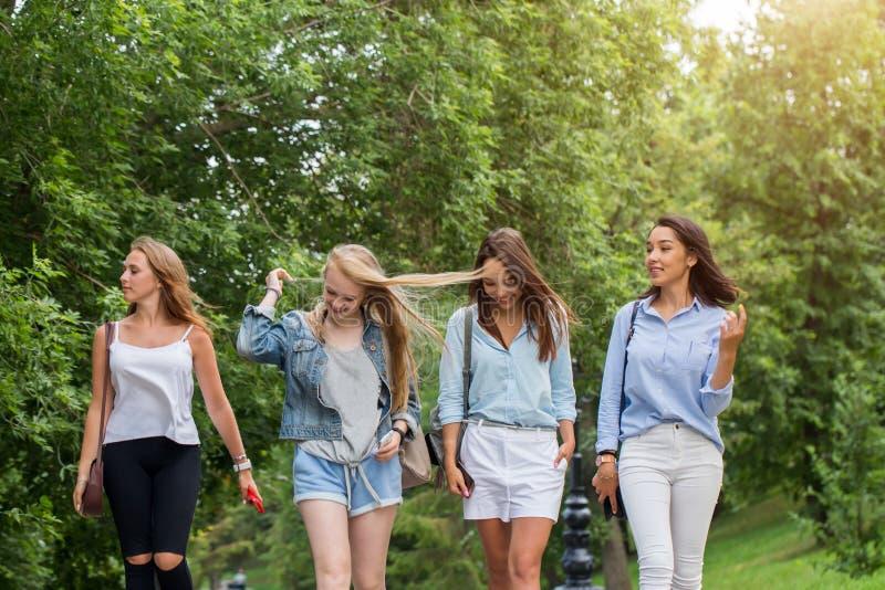 Feche acima de um grupo de quatro amigas que vão em casa após o passeio junto no parque estudantes fêmeas que andam após o estudo fotografia de stock royalty free