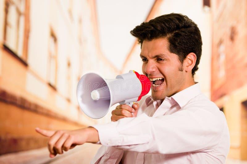 Feche acima de um homem considerável que grita com um megafone, apontando sua mão a alguém, em um fundo borrado da cidade fotografia de stock