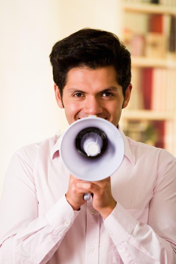Feche acima de um homem considerável que grita com um megafone em um fundo borrado fotografia de stock