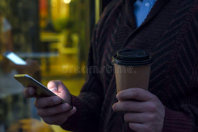 Feche acima de um homem de negócios usando o telefone celular e guardando o copo de papel O detalhe do close-up de businessmans e fotografia de stock royalty free