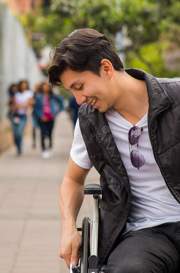 Feche acima de um homem deficiente de sorriso considerável dos jovens na cadeira de rodas, com uma mão na roda, nas ruas em Quito fotos de stock