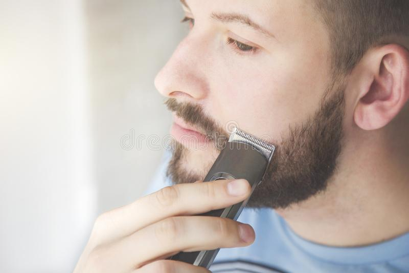 Feche acima de um homem novo considerável barbeia sua barba com uma lâmina elétrica Irritação de pele imagens de stock