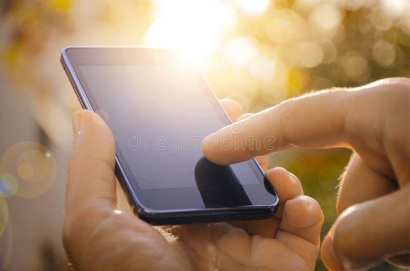 Feche acima de um homem que usa o telefone esperto móvel exterior