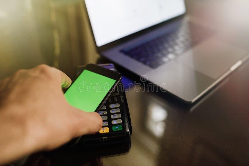 Feche acima de um pagamento do cartão que está sendo feito a betweem um homem e um garçom foto de stock royalty free