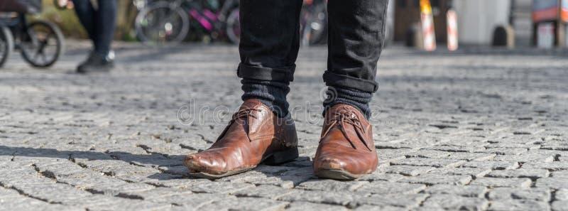 Feche acima de um par de sapatas gastadas com a sola aliviada da sapata foto de stock