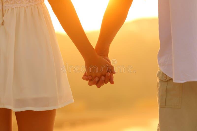 Feche acima de um par que guarda as mãos no por do sol foto de stock