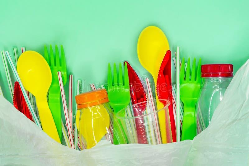 Feche acima de um plástico de reciclagem no saco branco no fundo verde imagem de stock