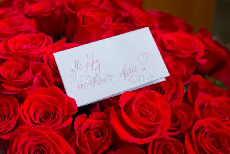 Feche acima de um ramalhete bonito de rosas vermelhas com um cartão feliz do dia de mães Conceito do dia do ` s da matriz feriado imagem de stock royalty free