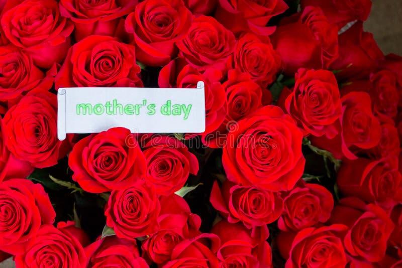 Feche acima de um ramalhete bonito de rosas vermelhas com um cartão feliz do dia de mães Conceito do dia do ` s da matriz feriado imagem de stock