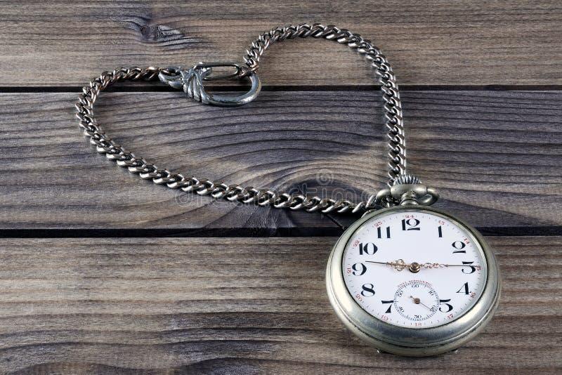 Feche acima de um relógio de bolso antigo em uma tabela de madeira antiga foto de stock