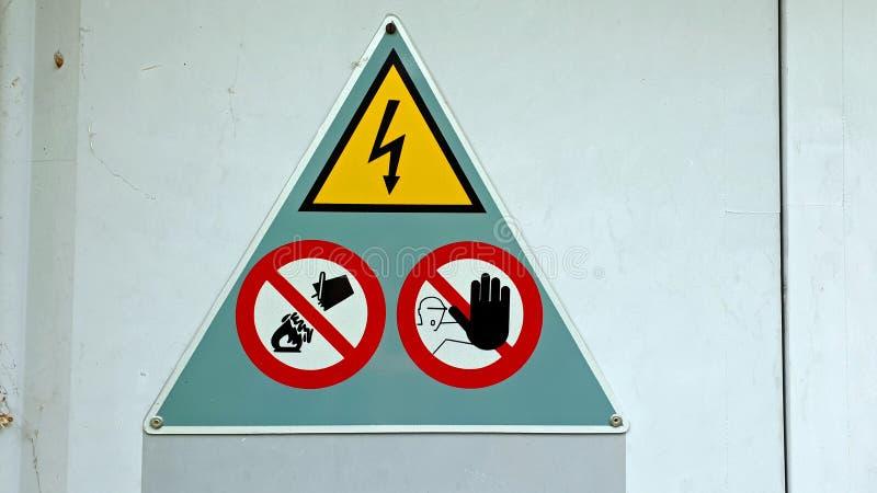 Feche acima de um sinal de aviso múltiplo em uma placa de metal fotos de stock