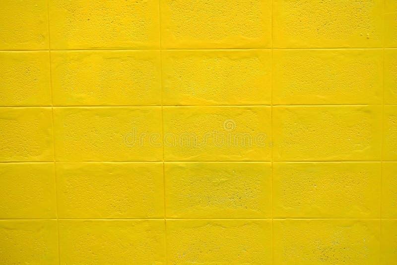 Feche acima de um teste padrão quadrado da parede amarela do cimento fotografia de stock royalty free