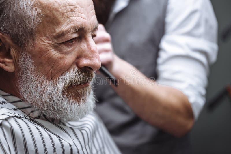 Feche acima de um trabalho do cabeleireiro s para um ancião considerável na barbearia fotos de stock