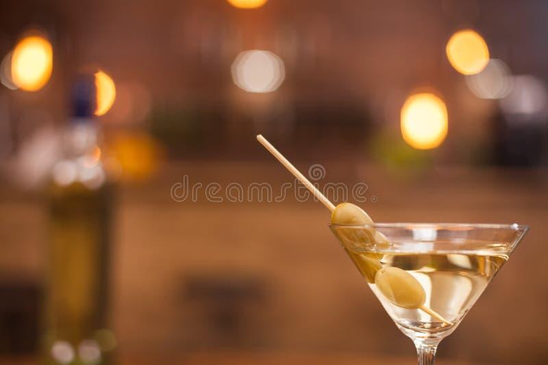 Feche acima de um vidro com martini e do contador borrado do baronete na parte traseira foto de stock royalty free