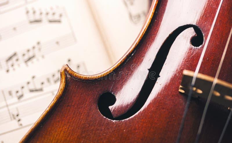 Feche acima de um violino velho nas notas de papel imagens de stock royalty free