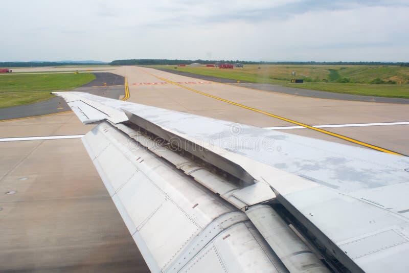 Feche acima de uma asa de um avião com aletas acima durante Taxiing na pista de decolagem fotos de stock royalty free