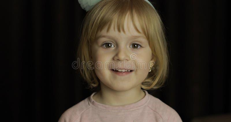 Feche acima de uma cara bonito loura pequena da menina Sorriso da menina inside Tiro do retrato foto de stock royalty free