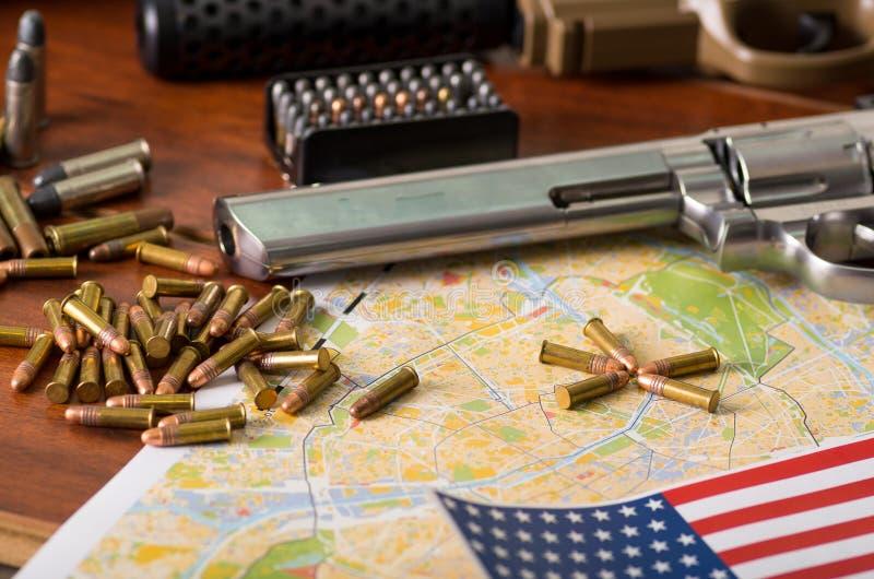 Feche acima de uma espingarda e de um revólver, correia de cartucho com balas com uma bandeira borrada do Estados Unidos em um ma fotografia de stock royalty free