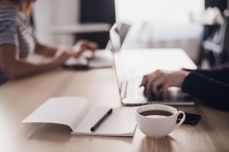 Feche acima de uma imagem de duas mulheres de negócios que usam o tablet pc e o portátil Caderno com pena e xícara de café no fotografia de stock royalty free