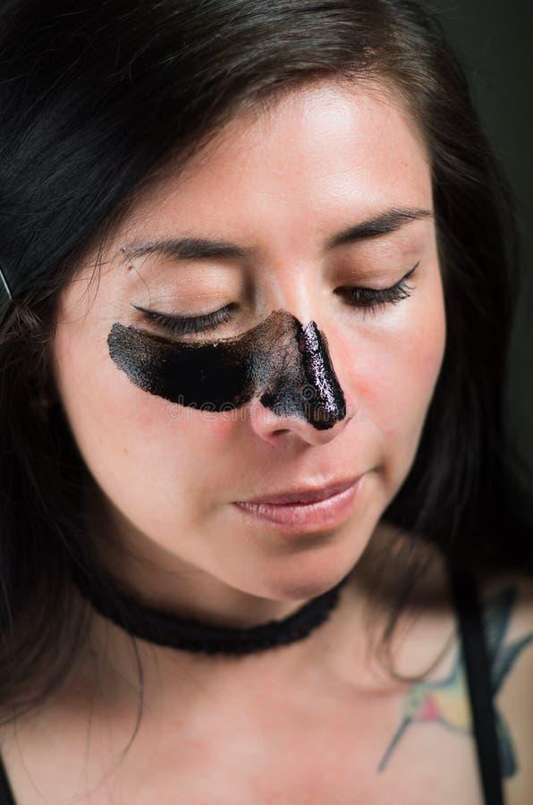 Feche acima de uma jovem mulher da beleza que aplying uma máscara preta para limpar a pele imagens de stock