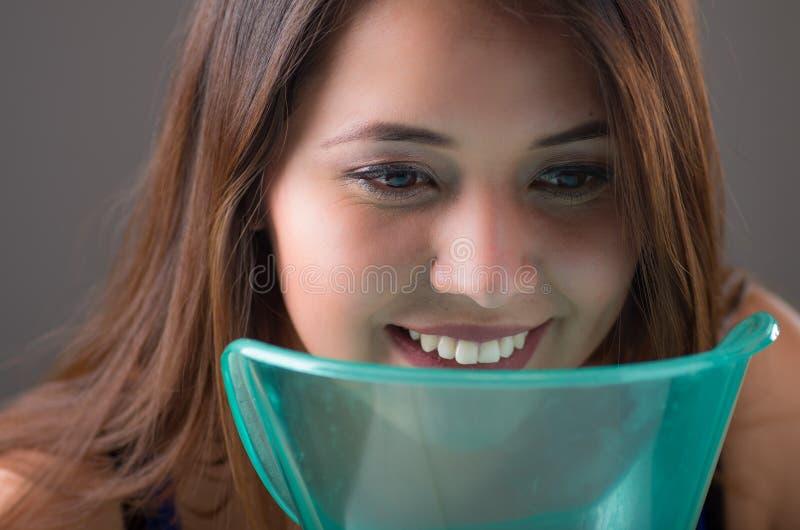 Feche acima de uma jovem mulher que faz a inalação com uma máquina do nebulizer do atomizador no fundo cinzento fotografia de stock