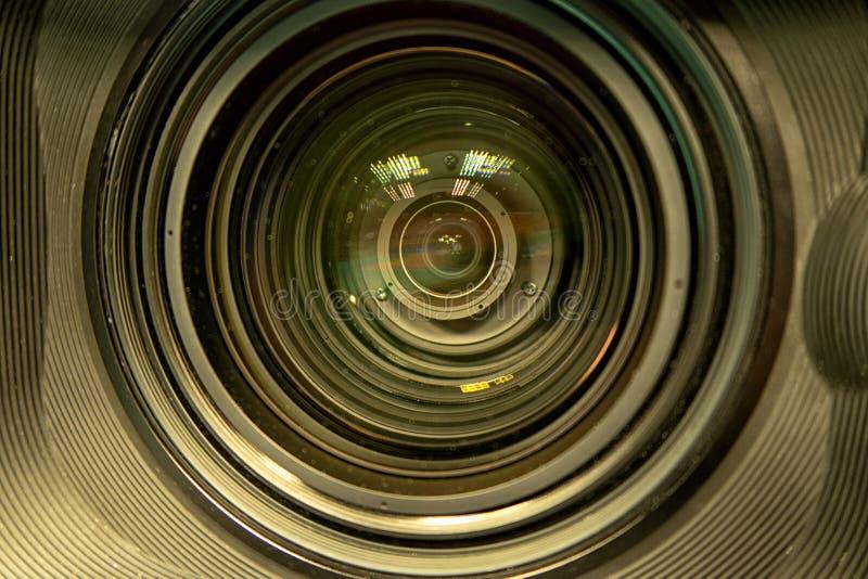 Feche acima de uma lente da televisão em um fundo escuro foto de stock