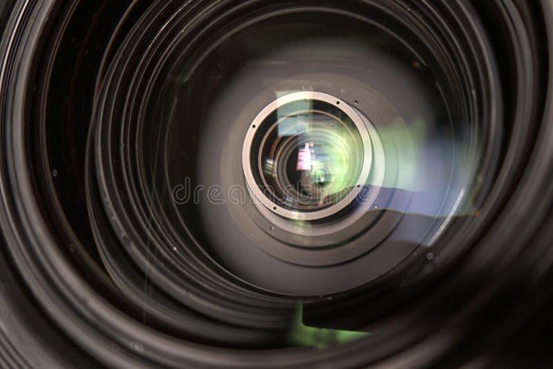 Feche acima de uma lente da televisão em um fundo escuro imagem de stock