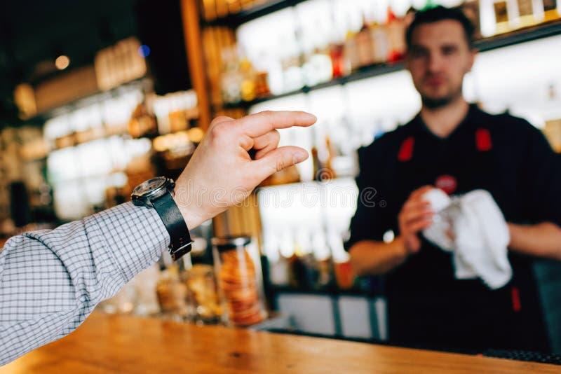 Feche acima de uma mão do ` s do cliente que mostra uma parcela de álcool ao empregado de bar E esta poção deve ser derramada no  fotos de stock