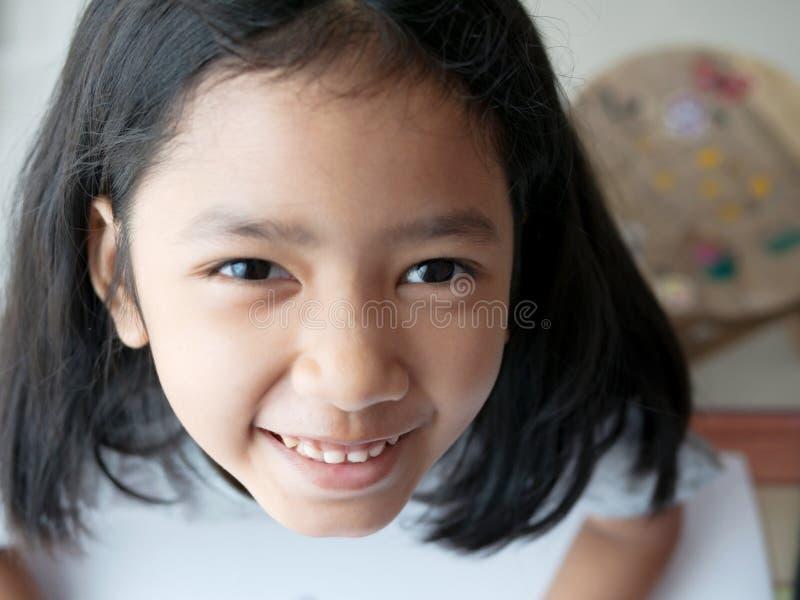Feche acima de uma menina asiática que olha acima uma câmera imagens de stock royalty free